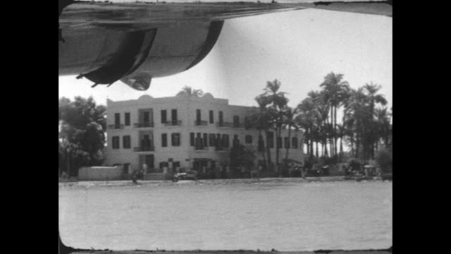 view from a short empire 'c' class flying boat as it is taxiing on the nile, passing by the winter palace hotel in luxor. - imperial palace hotel stock videos & royalty-free footage