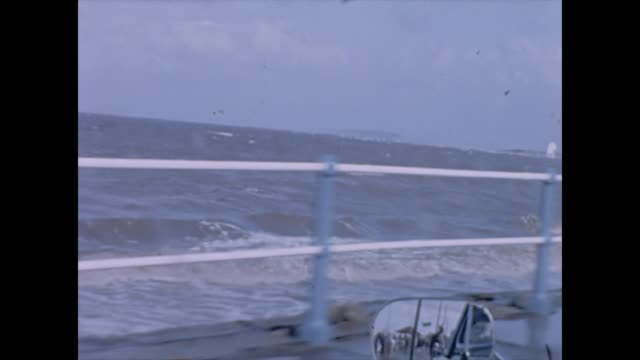 vidéos et rushes de view from a side window of a car by a sea wall with a rough sea 1965 - miroir ancien