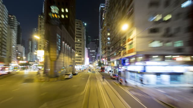 vídeos de stock, filmes e b-roll de tl, ws, pov view from a tram speeding through the streets of night-time hong kong / hong kong, china - time lapse de trânsito