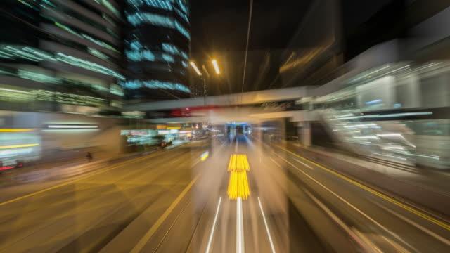 vídeos de stock, filmes e b-roll de tl, ws, pov view from a tram speeding through the streets of night-time hong kong / hong kong, china - ponto de vista de bonde