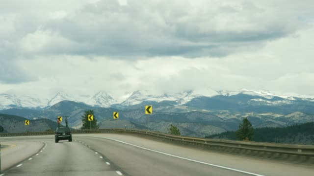 view from a vehicle driving westbound on curvy section of interstate 70 in the rocky mountains of colorado on a partly cloudy winter day - road sign stock videos & royalty-free footage