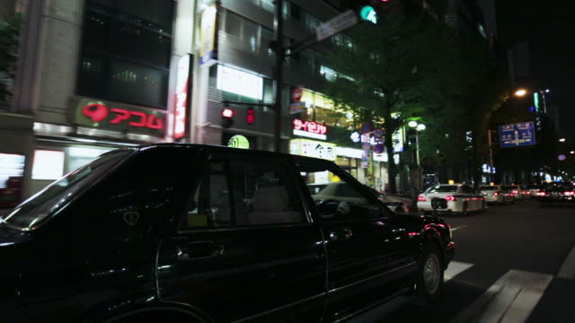 pov, ms view from a vehicle travelling through tokyo's shinjuku district at night / tokyo, japan - 移動中点の映像素材/bロール