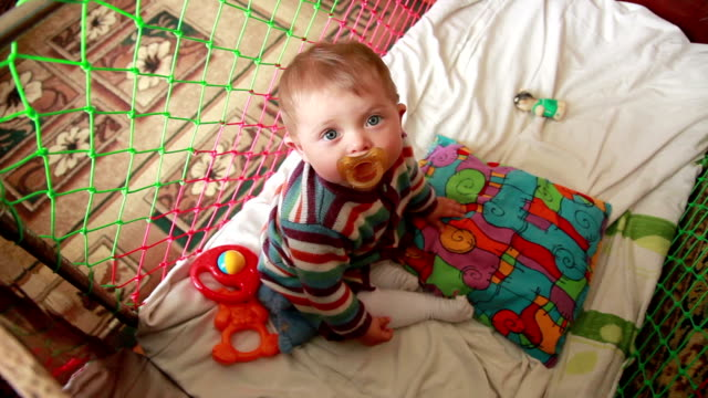 view from above of a baby sitting in the crib - pacifier stock videos and b-roll footage