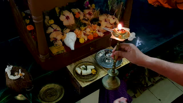 view from above of a place of worship/inside of temple showing human hand doing aarati (prayer) holding brass bell and candle lamp (diya) with religious offering (banana  fruits), flowers, holy coconut with sacred thread- 4k stock video - conch stock videos & royalty-free footage
