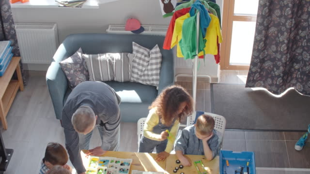 view from above of little kids playing with construction set - top garment stock videos & royalty-free footage