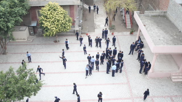view from above of the backyard of the high school building with boys wearing uniform during class break - only boys stock videos and b-roll footage