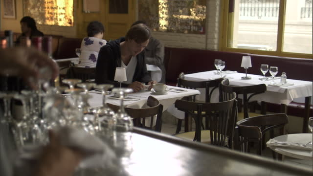 selective focus ms view from bar as man sits alone at restaurant table/ r/f bartender drying glass/ buenos aires, argentina - loneliness stock videos and b-roll footage