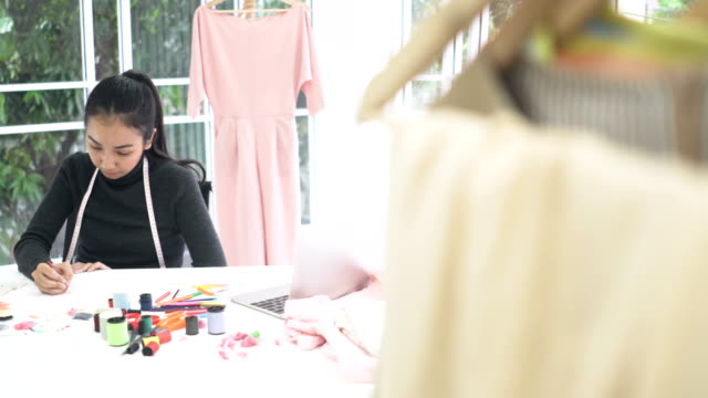 vídeos de stock, filmes e b-roll de vista por trás do cabideiro: projeto de designer de moda feminina e escrever no escritório em casa - 20 29 years