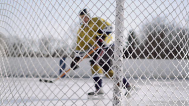 SM MS View from behind net of hockey player shooting puck into goal/ Long Island, NY