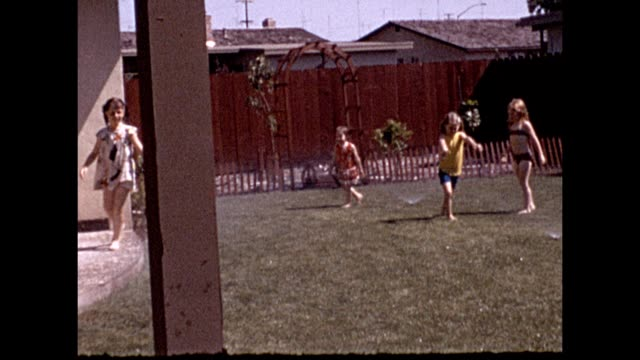 view from behind of a child sitting on a porch in a costume with a cat in modesto california four female children playing the backyard of a suburban... - veranda stock videos & royalty-free footage