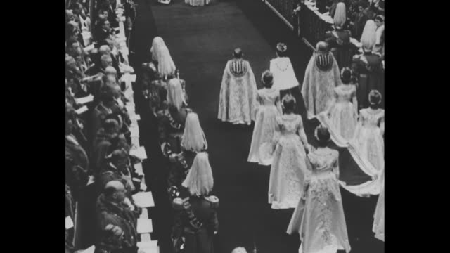 view from behind of various dignitaries walking down aisle of abbey flanked by life guards guests standing in stalls on either side / shot of guests... - coronation of queen elizabeth ii stock videos and b-roll footage