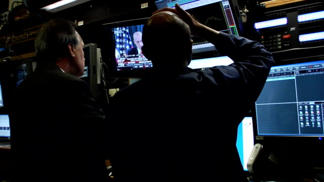 view from behind traders watching henry m paulson on tv monitor on trading floor of new york stock exchange new york city - 2008 stock videos and b-roll footage
