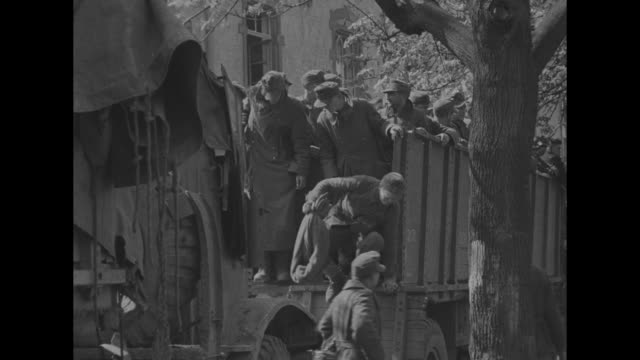 view from behind us soldier on top of tank guarding crowd of german prisoners in front of building / view from front of two soldiers on top of tank... - prigioniero di guerra video stock e b–roll