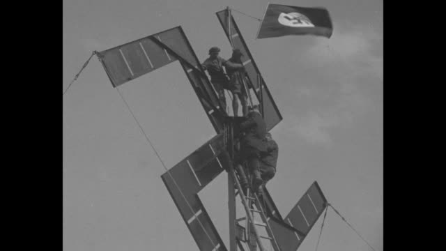 view from below of large swastika on scaffold three men on scaffold / closer view of men on scaffold nazi flag flying at top of scaffold / shot of... - nazi swastika stock videos and b-roll footage