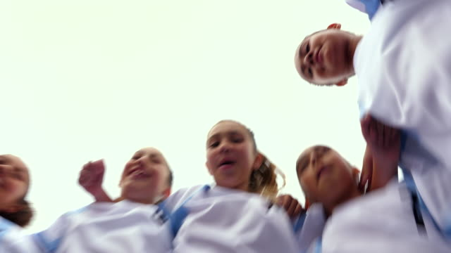 pan view from below of smiling young female soccer players in huddle before game - children only stock videos & royalty-free footage