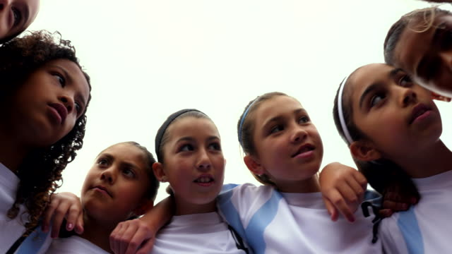 pan view from below of smiling young female soccer players in huddle - part of a series stock-videos und b-roll-filmmaterial