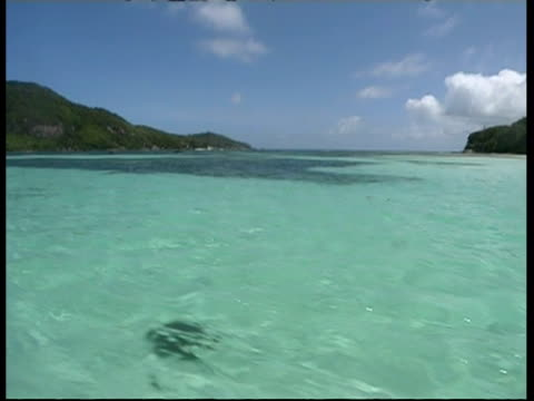 WA View from boat as it travels through clear water, framed by tree covered islands, Marine National Park, Seychelles