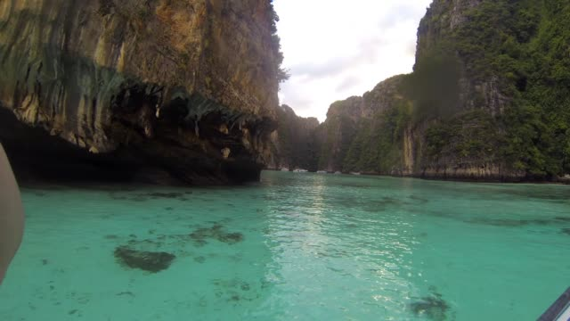 view from boat in clear, shallow bay between islands in thailand - insel phi phi le stock-videos und b-roll-filmmaterial