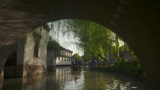 WS POV View from boat moving through canal under arch bridge, Zhouzhuang, Kunshan, Jiangsu province, China