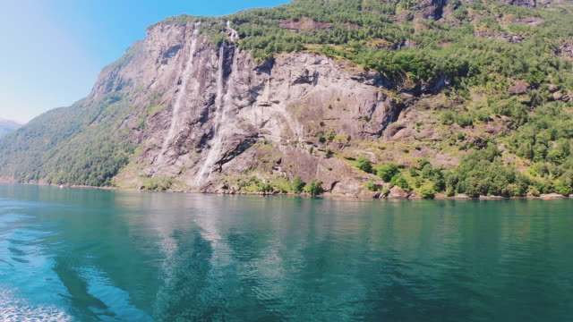 view from boat of seven sisters waterfall and green fjord in geiranger - fjord stock videos & royalty-free footage