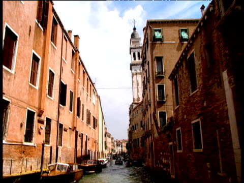 view from boat traveling down venetian canal tall buildings on either side and church spire against blue sky venice - 尖塔点の映像素材/bロール