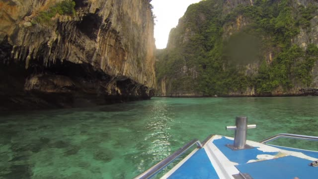 view from boat travelling on clear, shallow ocean beside islands in thailand - insel phi phi le stock-videos und b-roll-filmmaterial