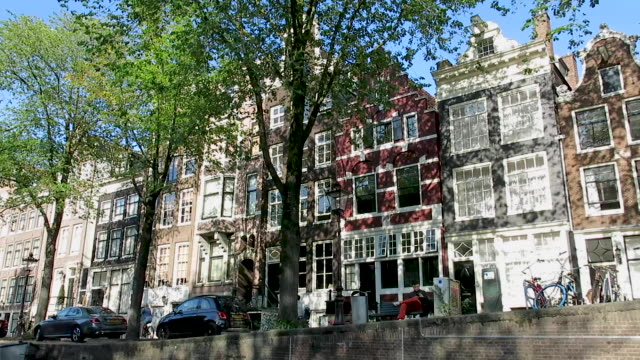 view from canal boat along classic amsterdam architecture - amsterdam video stock e b–roll