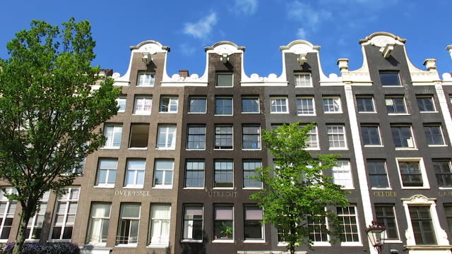 view from canal boat along classic amsterdam architecture - amsterdam stock videos & royalty-free footage