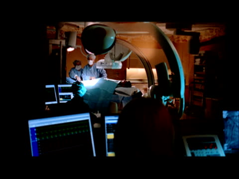 stockvideo's en b-roll-footage met ms, tu, td, view from cardiac catheterization control room into operating room, swedish american hospital, rockford, illinois, usa - operatiekleding