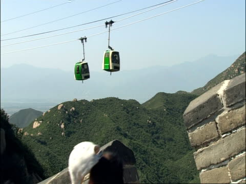 View from Great Wall of China battlements across to cable car, tourists move past camera, Badaling, China