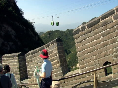 view from great wall of china battlements across to cable car, tourists walk past camera, badaling, china - badaling great wall stock videos & royalty-free footage
