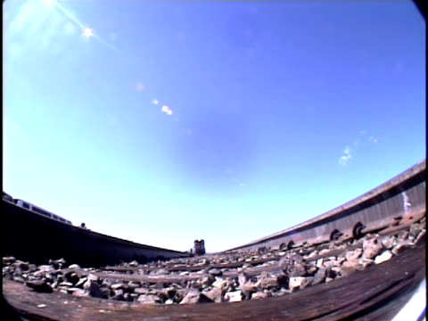 ms, fish eye, view from ground in middle of railroad tracks, train approaching and passing overhead, pueblo, colorado, usa - pueblo colorado stock videos & royalty-free footage