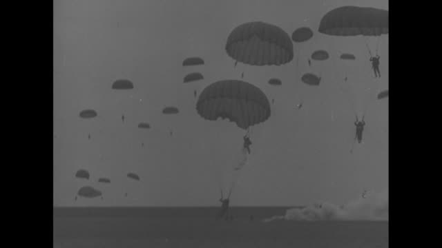 View from ground of airplanes dropping paratroopers / shot from plane of paratroopers / paratroopers landing / solders charging across battlefield /...