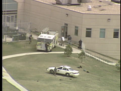 vídeos de stock, filmes e b-roll de view from helicopter aerial view of school police take cover behind fire truck advance toward the school and fire shots / on april 20th two teens... - columbine