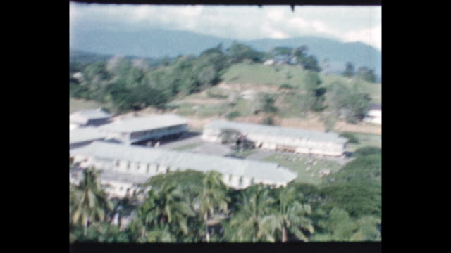 View from helicopter of children and teacher lined up to watch helicopter takes off with view of waving children and school and surrounding area from...