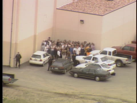 vídeos de stock, filmes e b-roll de view from helicopter police drag dead body people huddled together in corner of building / on april 20th two teens went on a shooting rampage at... - columbine