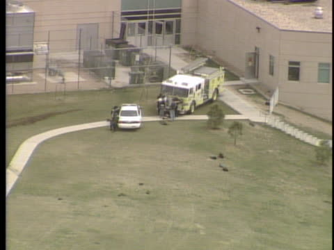 vídeos de stock, filmes e b-roll de view from helicopter police take cover behind fire truck people gathering on street away from the school / on april 20th two teens went on a shooting... - columbine