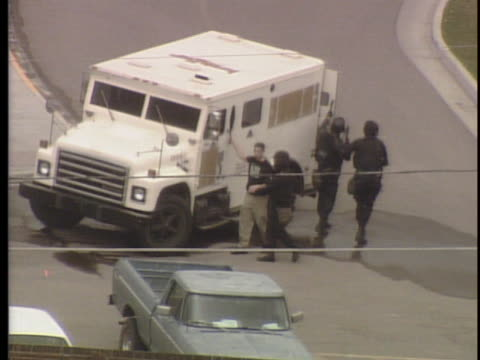 vídeos de stock, filmes e b-roll de view from helicopter zoom in on school and windows police use truck for cover as they try to get closer to the school and evacuate people / on april... - columbine