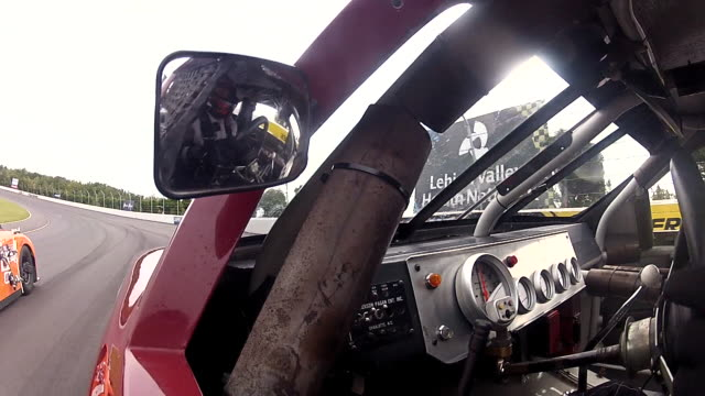 View from in car camera as race car driver stares ahead alertly and glances at rear view mirror.