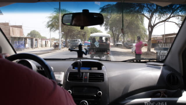 vídeos de stock, filmes e b-roll de view from inside a car looking at the road with rickshaws motorcycles and cars in piura peru - classified ad