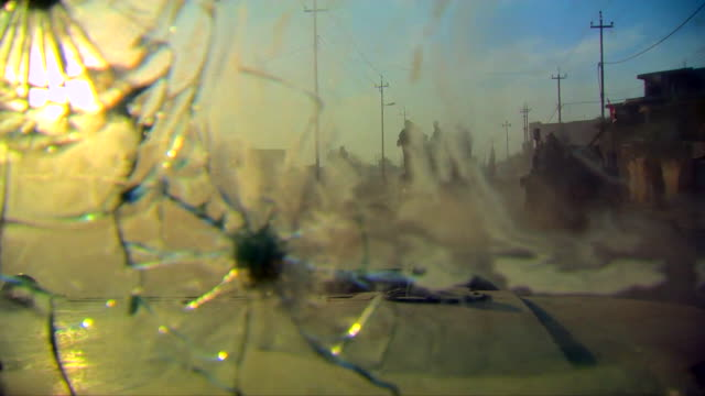 vídeos de stock, filmes e b-roll de view from inside an iraqi army armoured vehicle as it drives past the remains of a car bomb in western mosul - à prova de balas