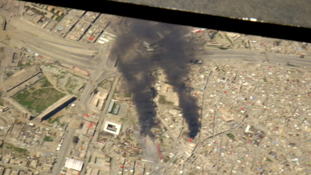 view from inside an iraqi army helicopter as it fires on islamic state targets in mosul - mosul stock videos and b-roll footage