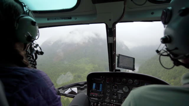 view from inside helicopter cockpit with misty mountains in vancouver, canada - helicopter stock videos & royalty-free footage