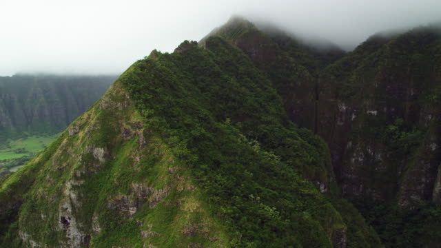 view from inside helicopter flying over a valley on the coast - kahuku stock videos & royalty-free footage