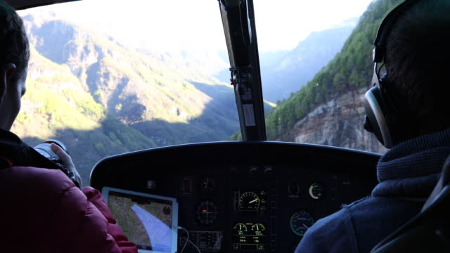 View from inside helicopter, while descending through mountains