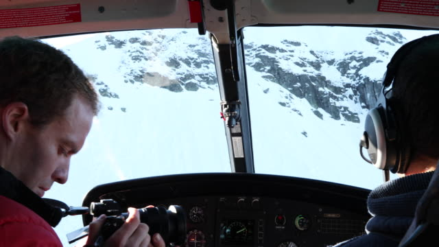 view from inside helicopter, while descending through mountains - helicopter stock videos and b-roll footage