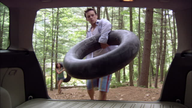 view from inside open trunk of car of young couple carrying inner tubes back to car from river / loading inner tubes into trunk / shutting trunk door / farmington river, connecticut - loading stock videos & royalty-free footage