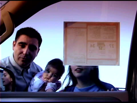 view from inside the car as a family walks up to look inside and check the sticker price. - price tag stock videos & royalty-free footage