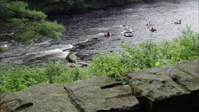 view from ledge of group of young men and woman floating down river on inner tubes / farmington river, connecticut - tubing stock videos and b-roll footage