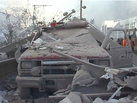 view from liberty st and west st. crushed fdny vehicle, wreckage of the world trade center tower two, firemen spraying water on fire, close up of... - september 11 2001 attacks点の映像素材/bロール
